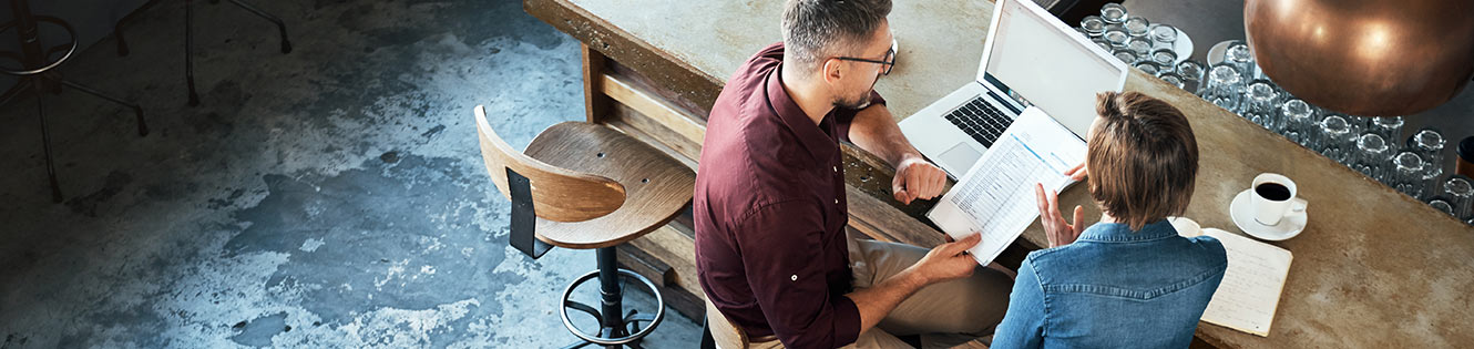 Couple with paperwork sitting at computer Header Image